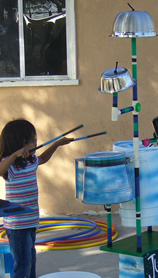 girl playing on junk music instruments